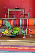 Outdoor furniture upholstered in bright stripes and bowls with tropical fruit on a wooden table; in the background a dining table in front of a bright, red wall