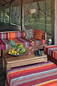 Cheery outdoor furniture upholstered in bright stripes and bowls with tropical fruit on a natural wooden table