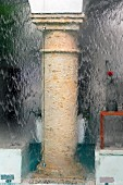 Blurred view of stone column in courtyard through glass wall