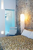 Designer bedspread on double bed against stone wall and modern, upholstered chair in front of interior window with view of shower area