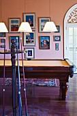 Billardzimmer mit apricotfarbener Wand und gerahmten Bildern