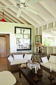Colonial-style coffee table and rattan sofa set in white wooden cabin