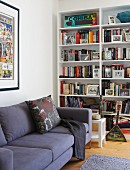 Modern, purple sofa in front of bookcase in corner of living room