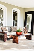 Colonial-style furniture on stone floor of terrace adjoining renovated house with arched windows