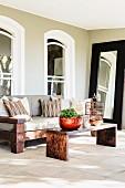Renoviertes Wohnhaus mit Rundbogenfenster und vorgelagerte Terrasse mit Möbel im Kolonialstil auf Steinboden