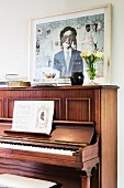 Sheet music on open piano and picture leaning on wall