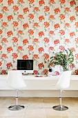 Designer swivel chairs at white console table against wall with floral wallpaper