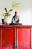 Statuette next to yellow orchid in pot on half-height, Oriental-style, red lacquer cabinet
