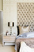 Masculine bedroom in shades of pale brown - fur blanket on bed against tall, quilted wall panel next to table lamp on bedside table
