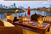 Lounge armchairs and lanterns on opium table on terrace with view of river and Brisbane skyline