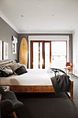 Simple double bed with wooden frame in room painted dark grey with large French window