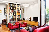 Red leather furniture in front of a book case doubling as a room divider
