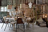 Festively set, candlelit table in barn-like interior with DIY wall made from vintage windows