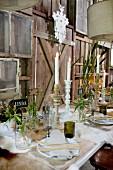 Festlich gedeckter Tisch mit brennenden Kerzen und Wiesenblumen in Gläsern vor rustikaler Holzwand