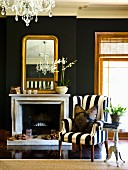 Black and white armchair next to an open fireplace and a gold framed mirror on a black wall
