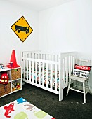 Nursery with wooden cot, shelves of toys & child's rug