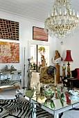 Ungebremste Sammelleidenschaft in Wohnraum mit postmodernem Spiegeltisch und Zebrafell