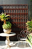 Palm-like plant on stone table and wire chair on patio with ornate metal grid on dark wall