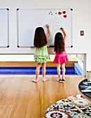 Two girls drawing on magnetic whiteboard