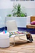 Liegestuhl & runder Beistelltisch auf deckartiger überdachter Terrasse mit Pool im Hintergrund
