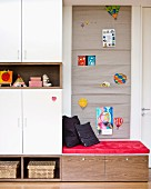 Seating area in child's bedroom with fabric wall hanging used as pinboard