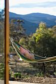 Hängematte mit Kissen über der Terrasse schwingend vor Landschaft mit Bergblick