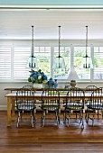 Windsor chairs at long rustic dining table in sunny dining room