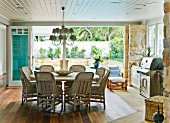 Dining set with large round table and wicker chairs below pretty chandelier; stainless steel barbeque below window