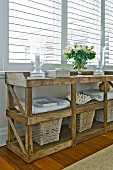 Storage baskets and fresh laundry below rustic wooden table; elegant candle lanterns and bouquet of white summer flowers on table top