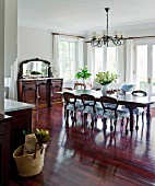 Reddish, shimmering precious wood takes command of this open kitchen-living room with traditional, antique style furniture
