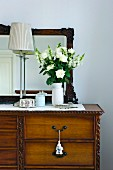 Bouquet of white flowers and table lamp on an antique chest of drawers with mirror