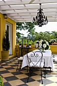 Dining area with delicate wrought iron furniture and wrought iron chandelier on a terrace with a diagonally laid checkerboard tile floor