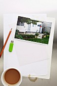 Photo of house next to pencil, USB stick & cup of coffee on sheet of paper