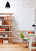 Desk and green shell chair next to modern wooden shelving against wallpaper with three dimensional pattern