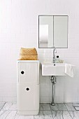 Half-height, white designer storage cabinet next to minimalist washstand against white tiled wall with integrated mirrored cabinet