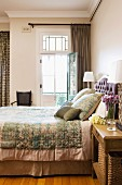 Double bed with elegant bedspread and matching scatter cushions next to open balcony door in traditional, elegant bedroom