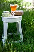 Refreshing drink and toiletries on white stool amongst green grass