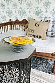 Dish of sliced citrus fruits on table and wooden bench with carved backrest against floral, fabric wallpaper