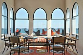 Tables and chairs in front of arched windows in lobby flooded with light; view of butterfly chairs on terrace with sea view through windows