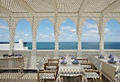 Pattern of light and shade on set tables below roof terrace pergola with view of sea through open, Oriental arches