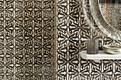 Shelf of bathroom utensils against black and white tiled wall with Oriental pattern