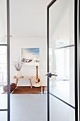 Blick durch offene Glastür, mit filigranem Metallrahmen, auf Beistelltisch mit Blumenvase neben Gitarre an Wand mit Bild