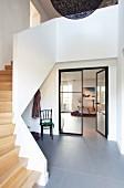 Offenes, modernes Treppenhaus mit Holztreppe und grauem Steinboden im Foyer, offene Glastür und Blick in Wohnraum