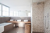 Shower with terrazzo-style tiles and modern washstand in background with two sinks below wide mirror on wall