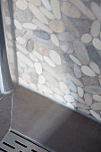 Corner of shower cubicle with drain cover and terrazzo-style wall