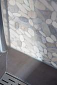 Ecke einer Duschkabine mit Abdeckplatte für Wasserablauf und Duschwand im Terrazzo-Look