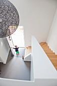 Dramatischer Blick von oben auf Designerhängeleuchte neben Treppenabgang und kleines Kind steht in offener Haustür