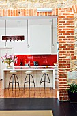 View though wide open doorway in brick wall of designer barstools at counter in open-plan fitted kitchen