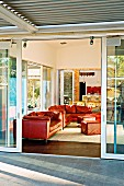 View from terrace through open sliding door of red leather sofa set in living room