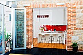Blick vom Anbau durch breiten Durchbruch in Ziegelwand in offene weiße Designerküche mit Barhockern an Theke